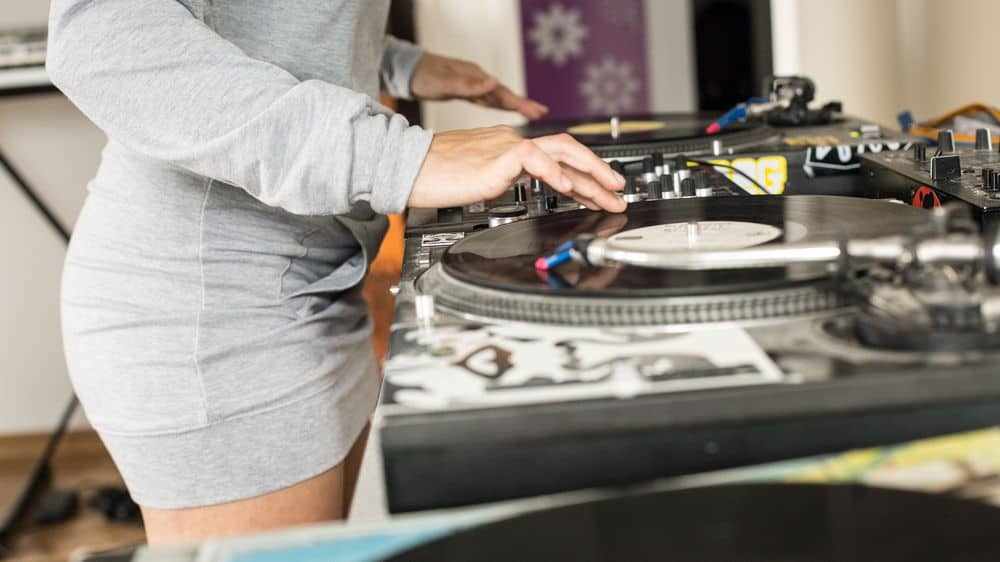 Woman DJ spinning on turntables